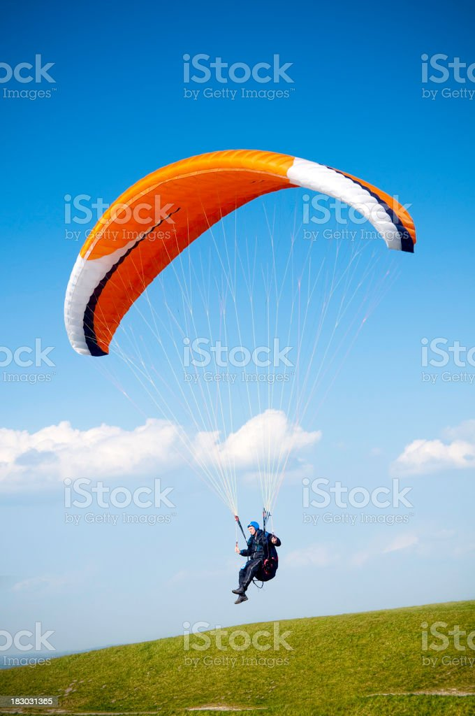 Paraglider with orange parachute against blue sky stock photo