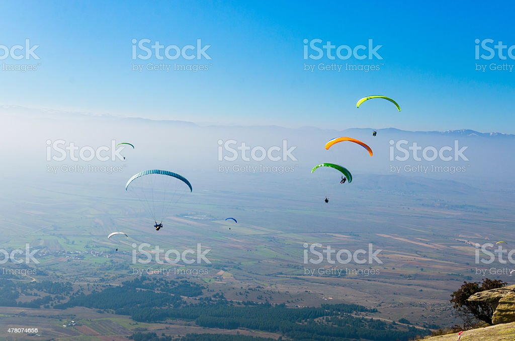 Paragliders at clear blue sky. Paragliding is extreme adrenaline sport. stock photo