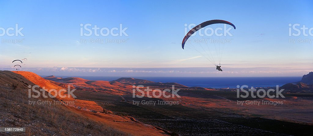 Paragliders flying during sunset stock photo