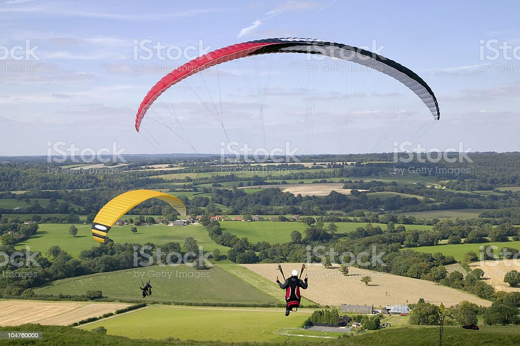 Paragliders over flat land on sunny day stock photo