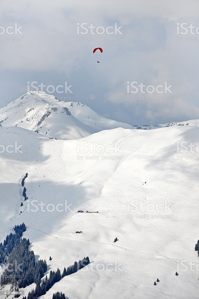Paragliding above snow covered mountains in the Alps stock photo