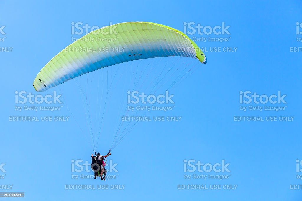 Paragliding in blue sky, instructor and beginner stock photo