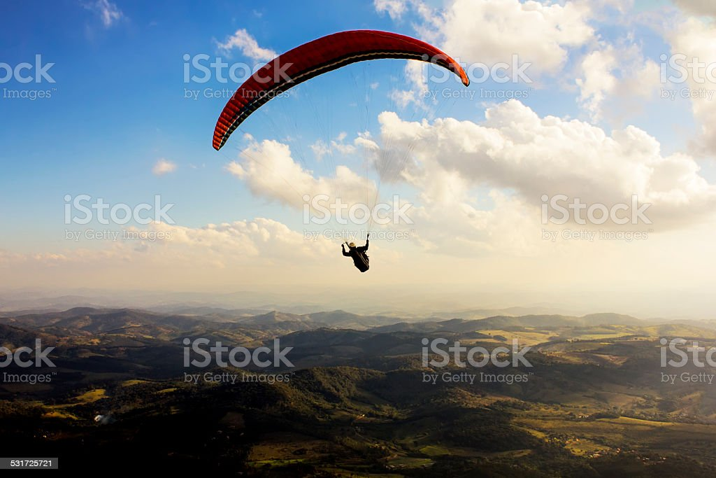 Paragliding Over Mountains at Sunset stock photo