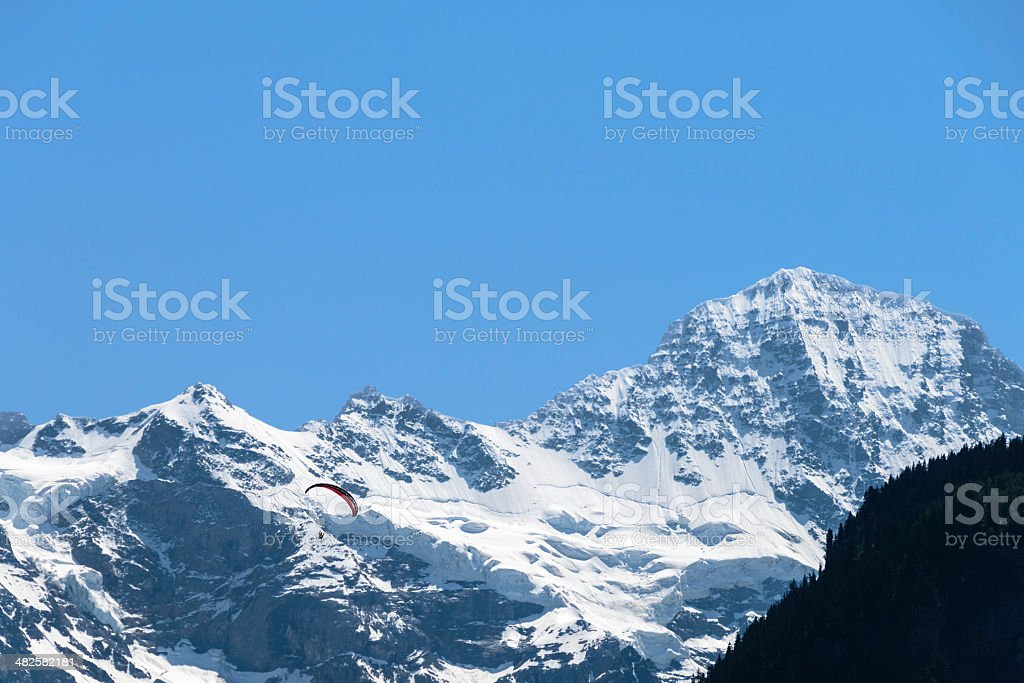 Paragliding over snow capped mountains royalty-free stock photo
