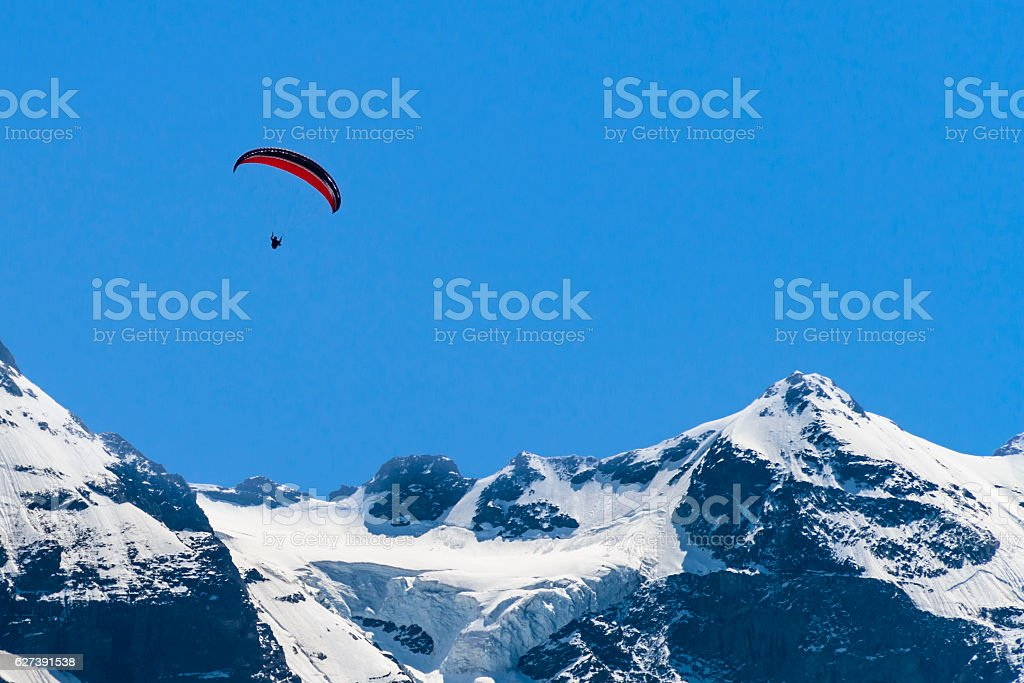 Paragliding over snow capped mountains stock photo