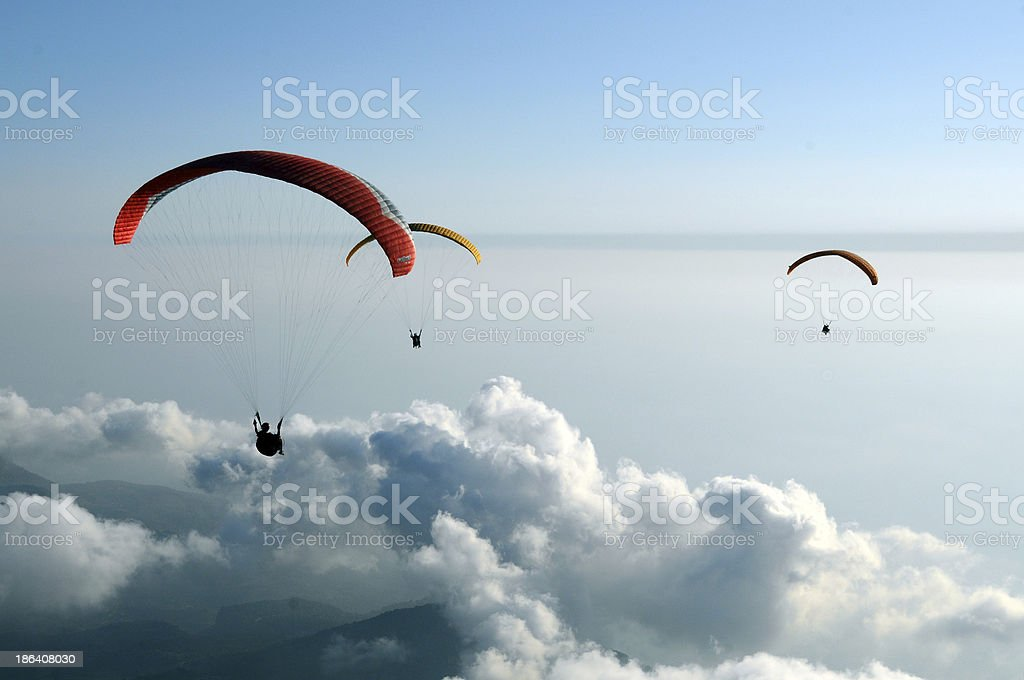 Paragliding over the white clouds stock photo