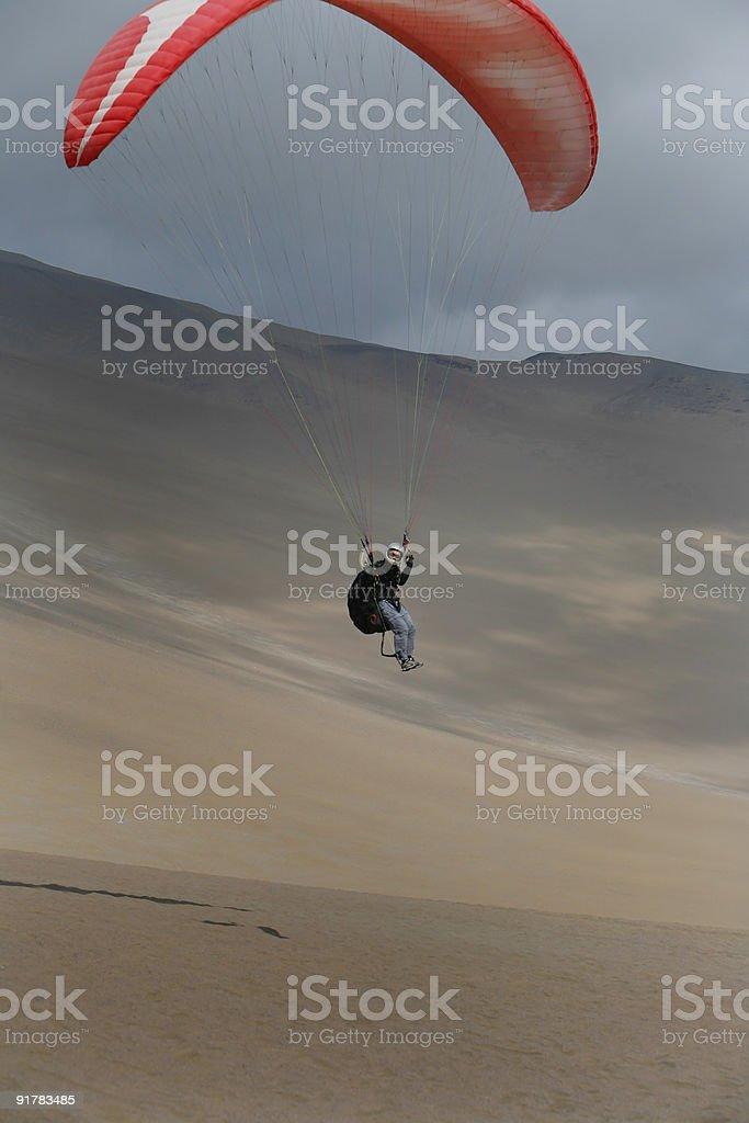 Paragliding Pilot Flying in the Desert stock photo