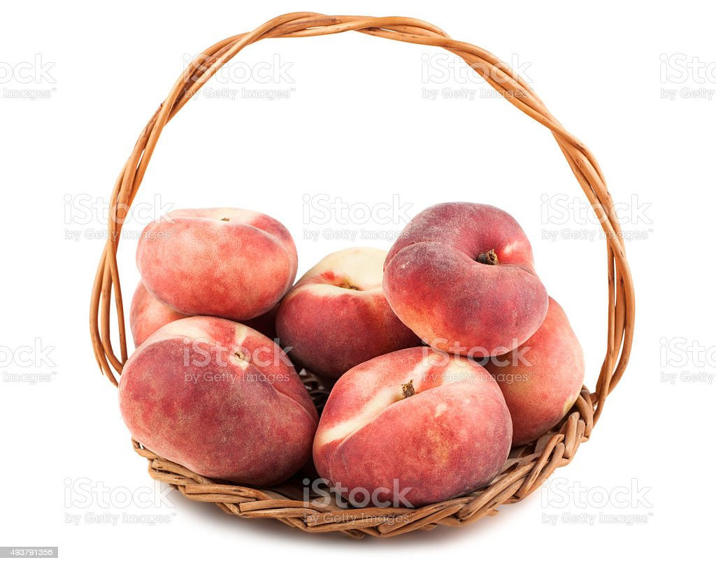 Paraguayos flat peaches in wicker basket stock photo