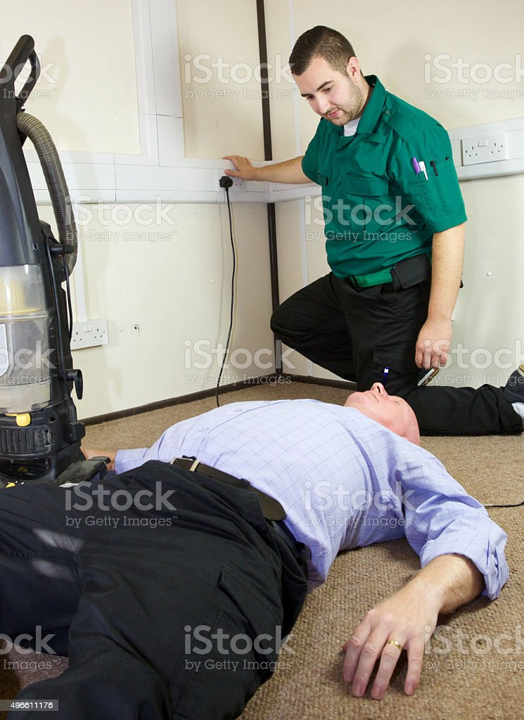 Paramedic attends an accident where a patient has been electrocuted stock photo