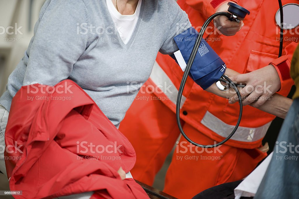 Paramedic measures the blood pressure with a sphygmomanometer stock photo