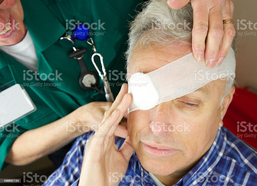 Paramedic nurse attending to a patient's eye after injury stock photo