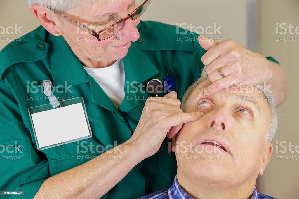 Paramedic nurse checking a patient's eye after an injury stock photo