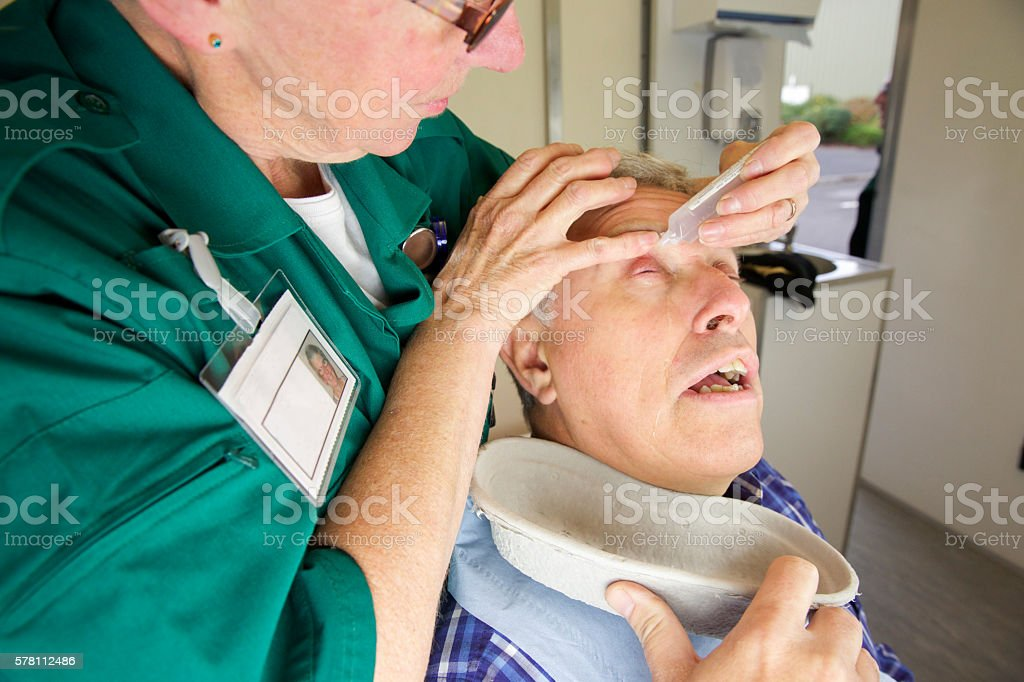 Paramedic nurse putting drops in a patient's eye after injury stock photo