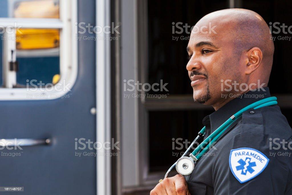 Paramedic standing by ambulance stock photo