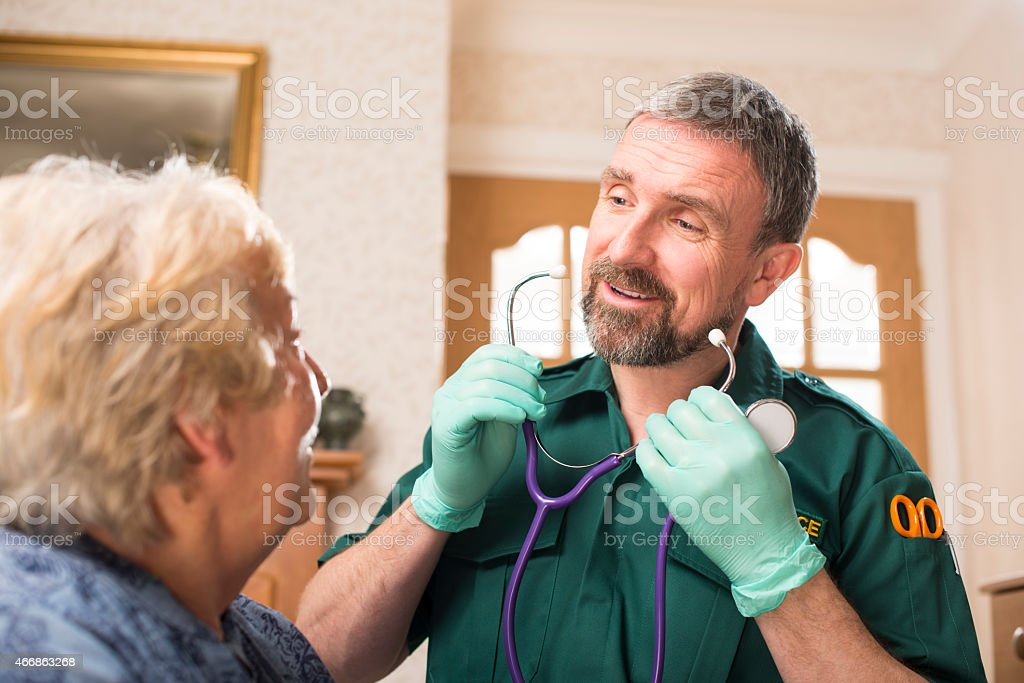 Paramedic treating senior patient at home stock photo