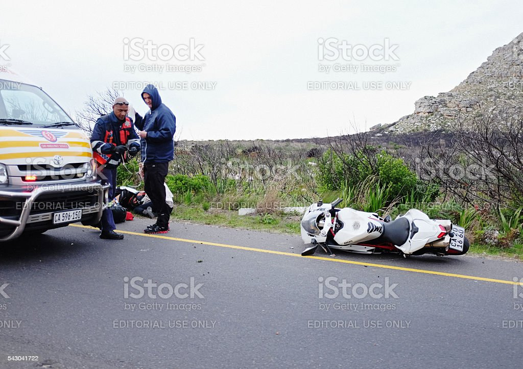 Paramedics aid crashed biker at motorcycle accident stock photo