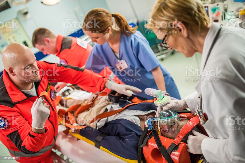 Paramedics and doctors in emergency room stock photo