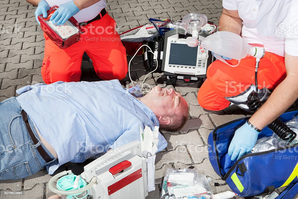 Medical emergency. Paramedics treating an unconscious victim on the...