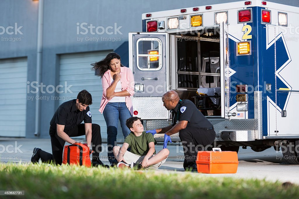 Paramedics helping boy with mother watching stock photo