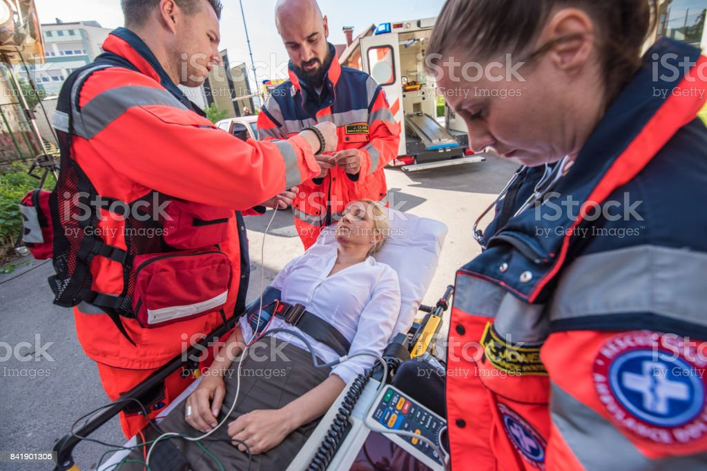 Female paramedics providing first aid to woman injured in car...
