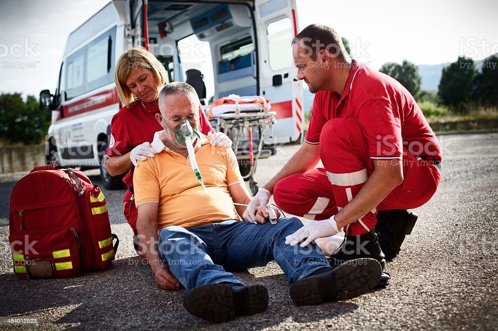 Paramedics succor a man with heart attack stock photo