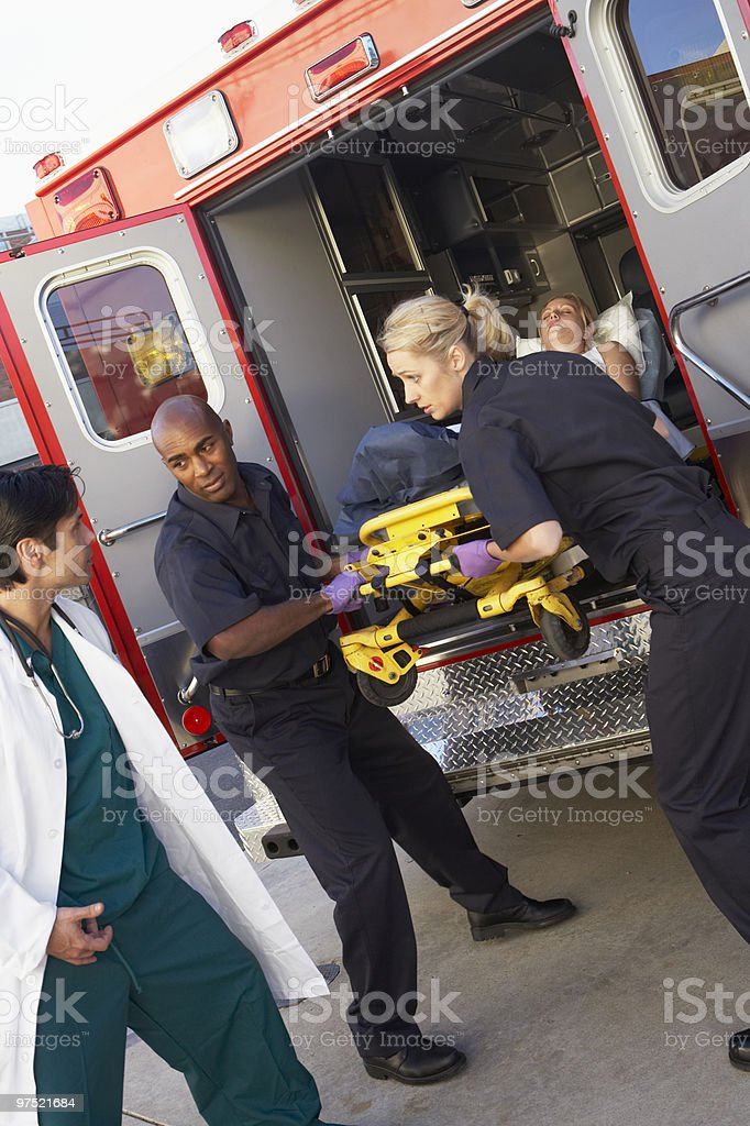 Paramedics unloading patient from ambulance for doctors help stock photo