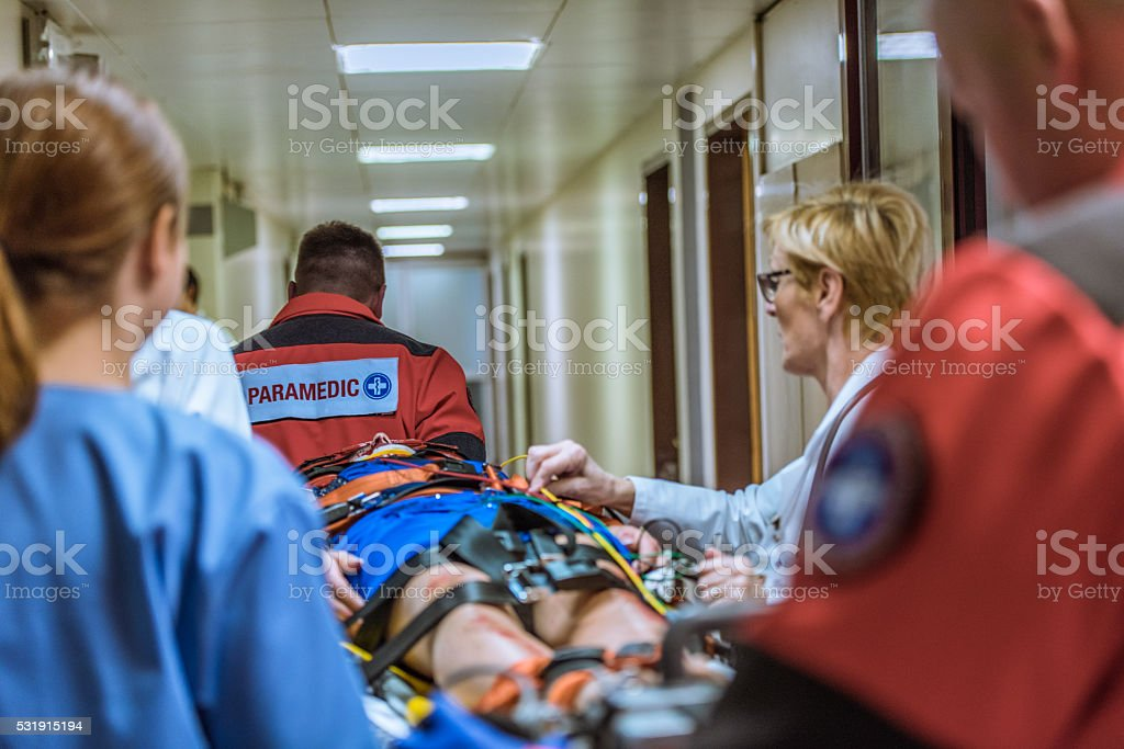 Paramedics wheeling patient in hospital stock photo