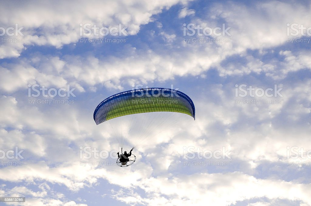 paramotor in the cloudy sky stock photo