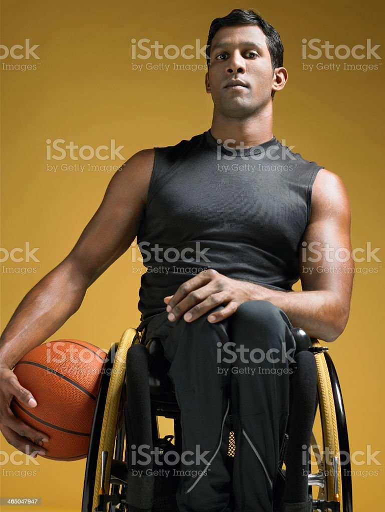 A paraplegic athlete on a wheelchair with a basketball stock photo