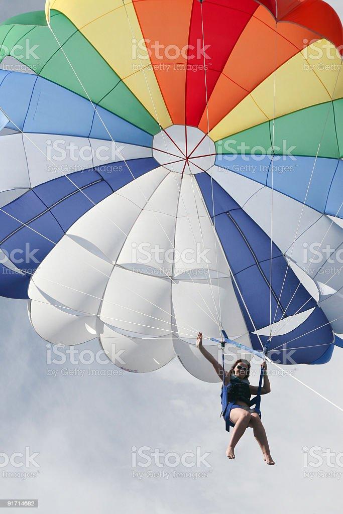 parasailer gliding across a blue sky stock photo