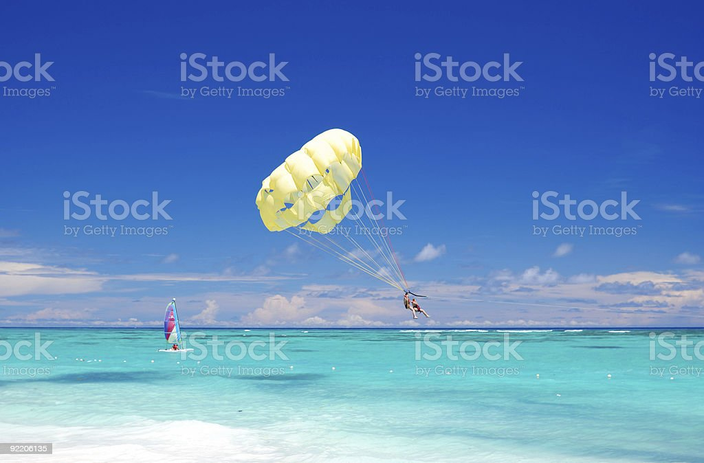 Parasailing and wind surfing off of Caribbean beach stock photo