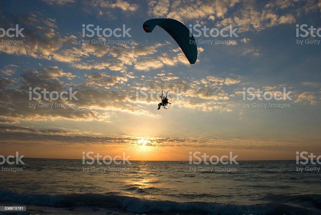 Parasailing Paragliding Over Ocean At Sunset Sunrise stock photo