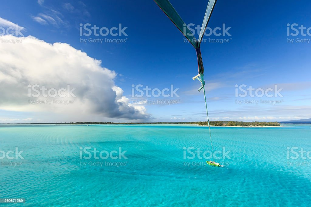 Parasaling in Bora Bora Over Crystal Clear Turquoise Water stock photo