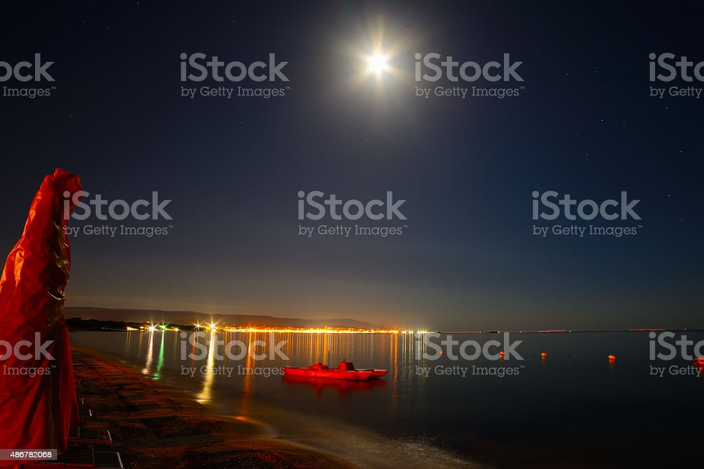 parasol and boat on a starry night in Alghero stock photo