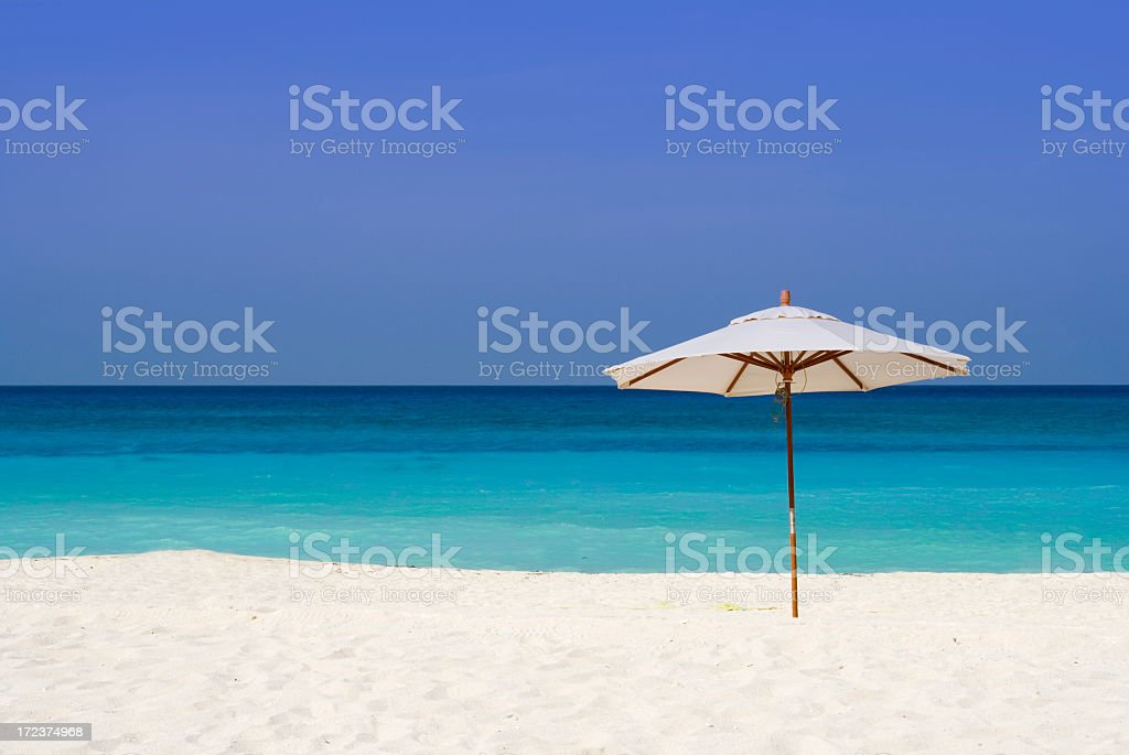 A parasol in the sand at a beach stock photo