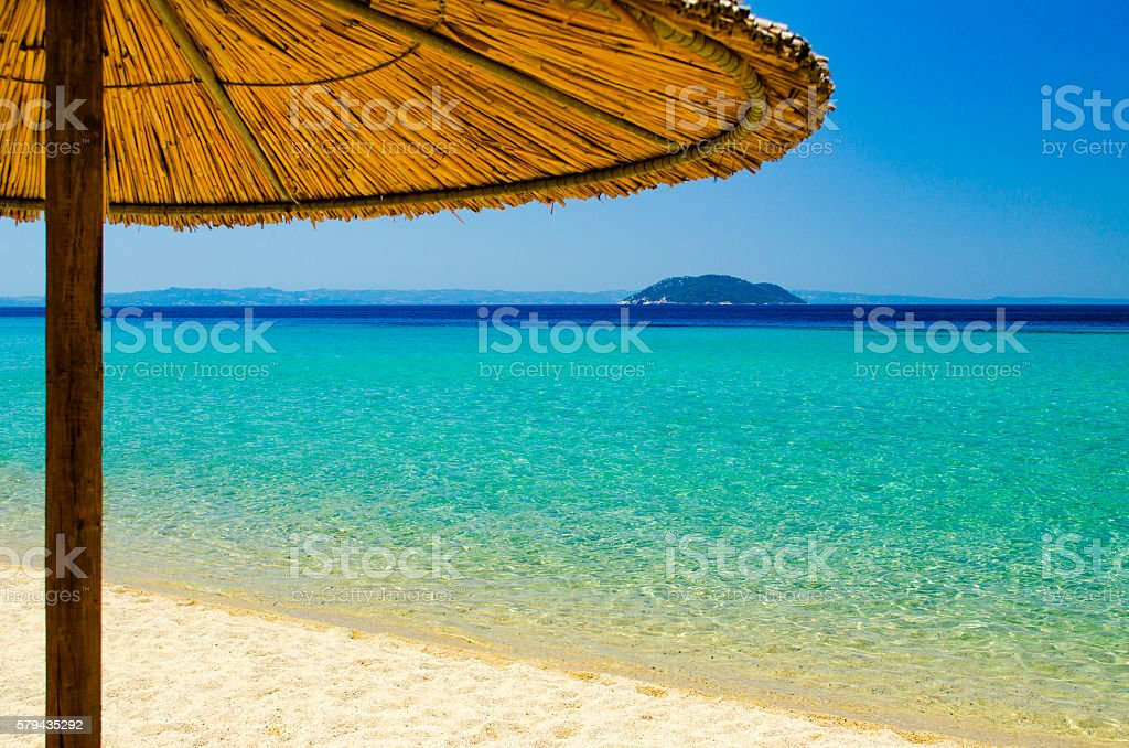 Parasol on beautiful beach and island in the background stock photo