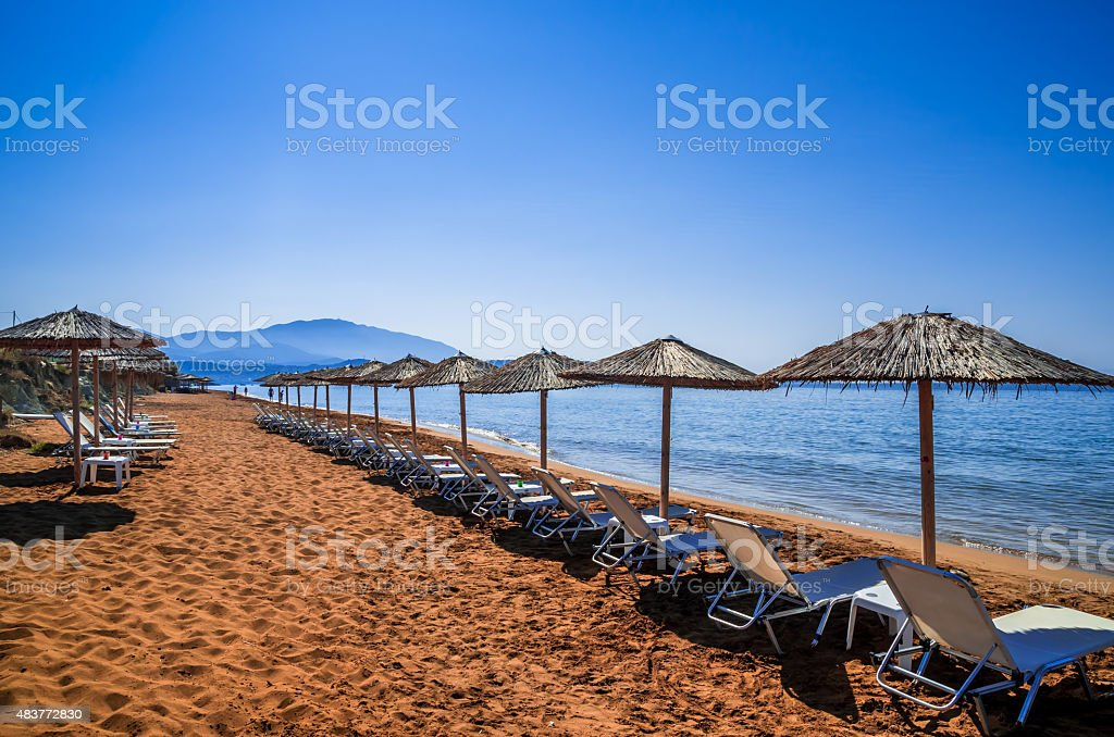 Parasols and tanning beds on the beach. stock photo