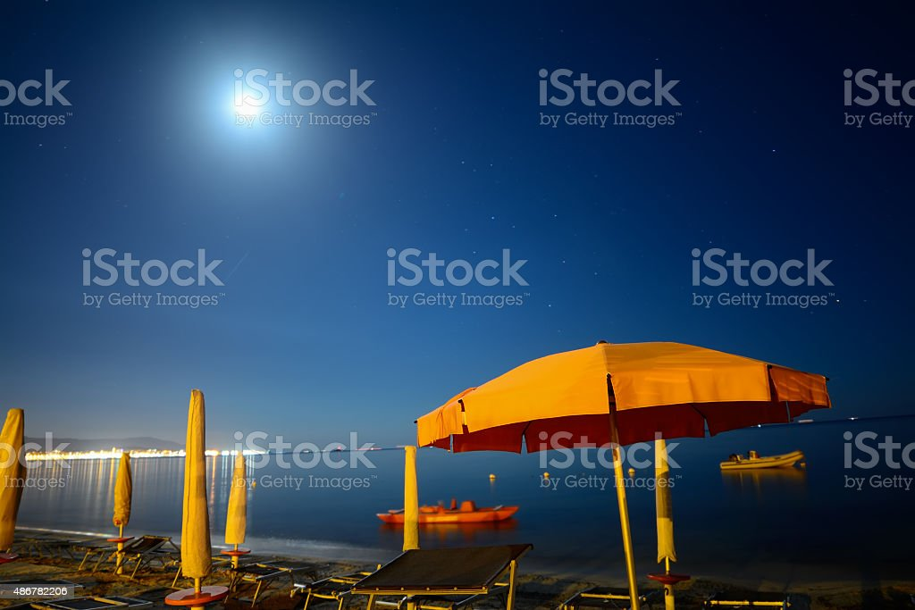 parasols by the sea under a bright moon stock photo