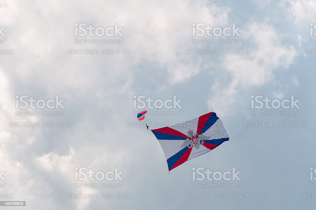 Paratrooper with giant Ministry of Defense flag against sky background royalty-free stock photo