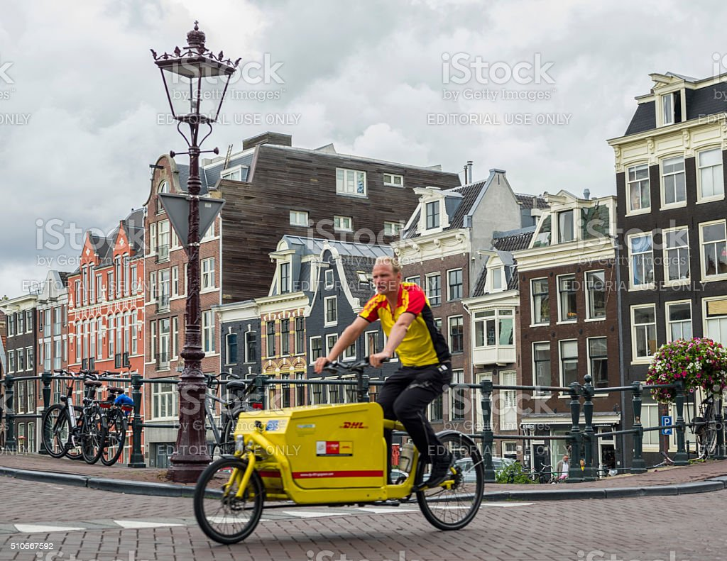 Parcel Delivery Man On Bike In Amsterdam stock photo