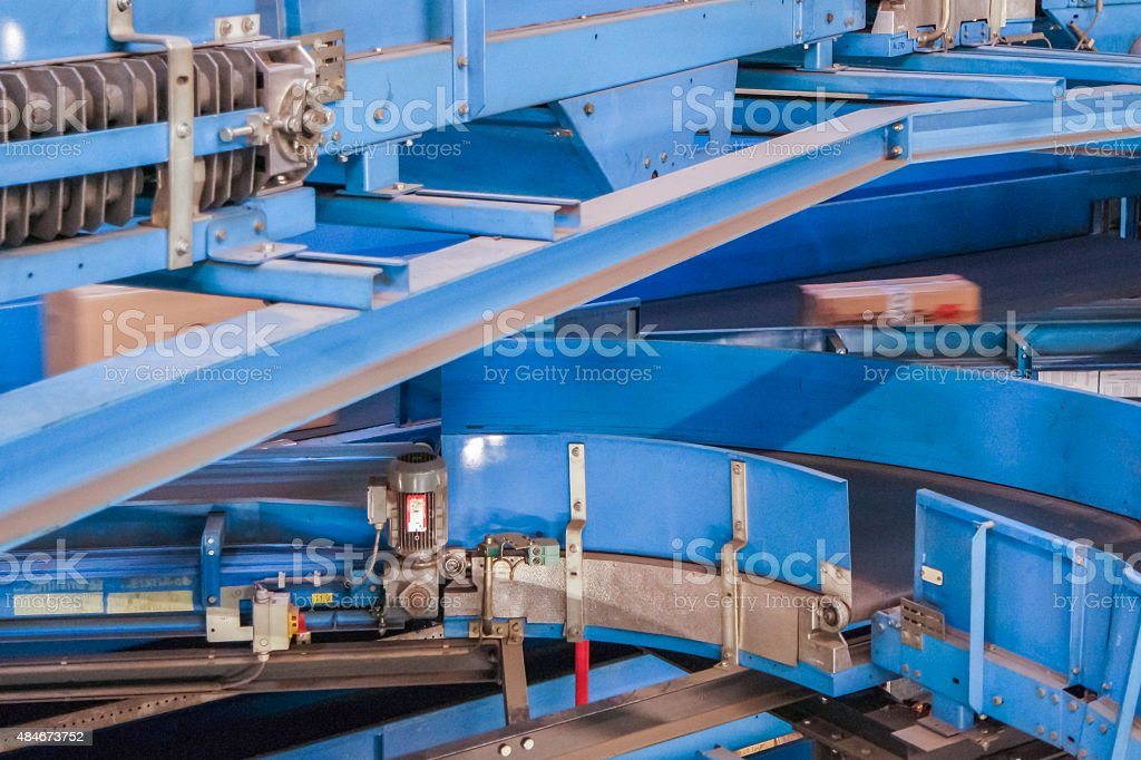 Parcels on conveyors with blurred industrial background stock photo