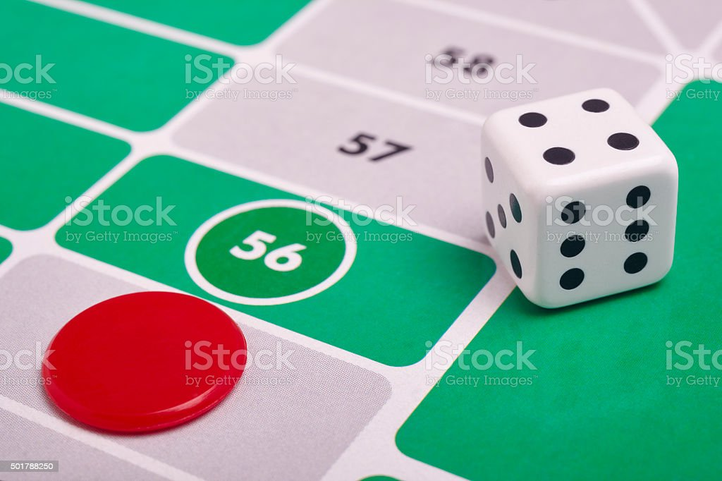 Parcheesi board game detail with dice and game piece stock photo