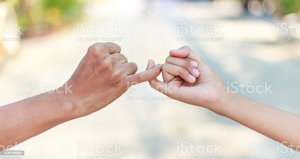 Parent and child hooking their fingers to make a promise stock photo