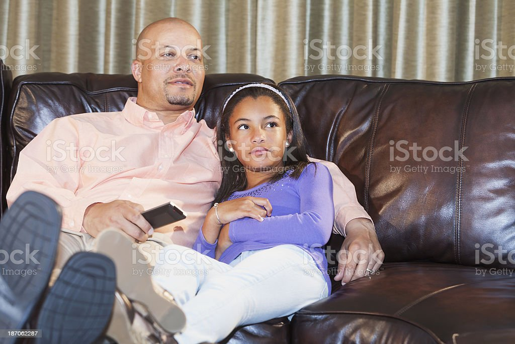 Parent and child sitting on living room couch watching TV stock photo