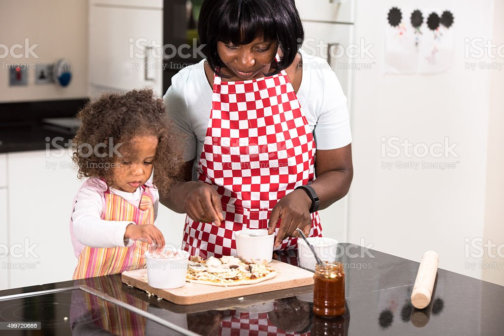 Parent/ Carer/ Childminder And Biracial Little Girl Making Pizza stock photo