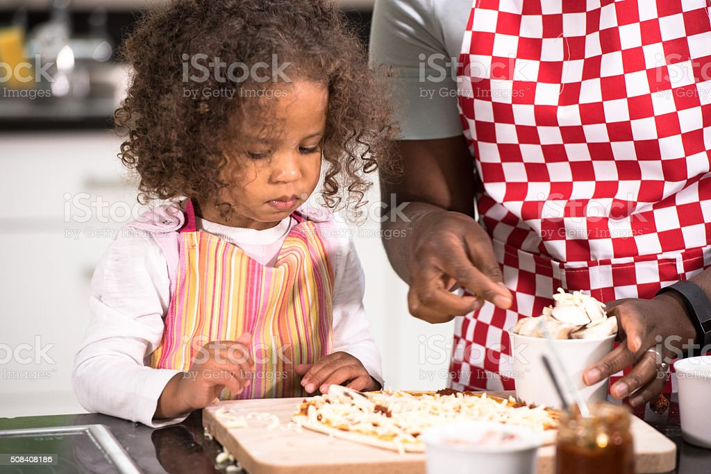 Parent/ Carer/ Childminder Making Pizza With  Biracial Little Girl stock photo