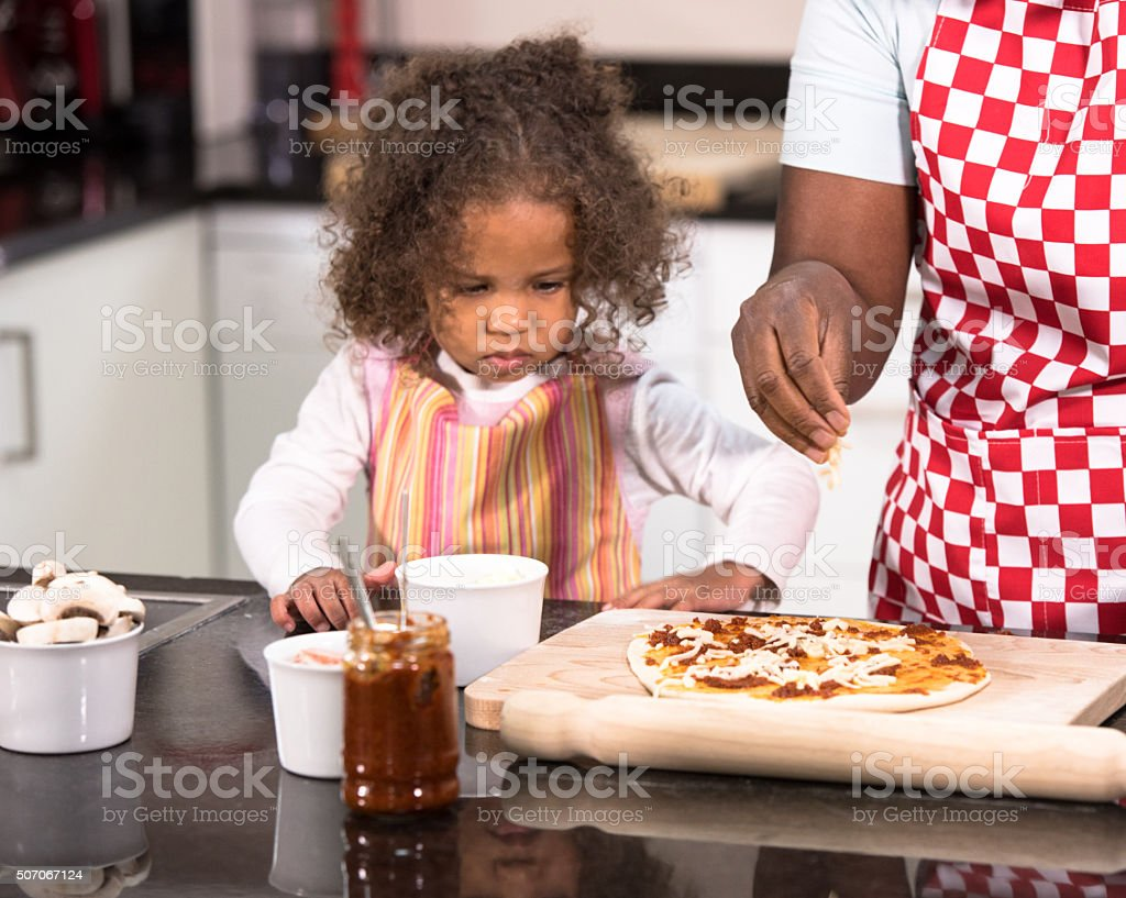 Parent/ CarerMaking Pizza With Biracial Little Girl stock photo
