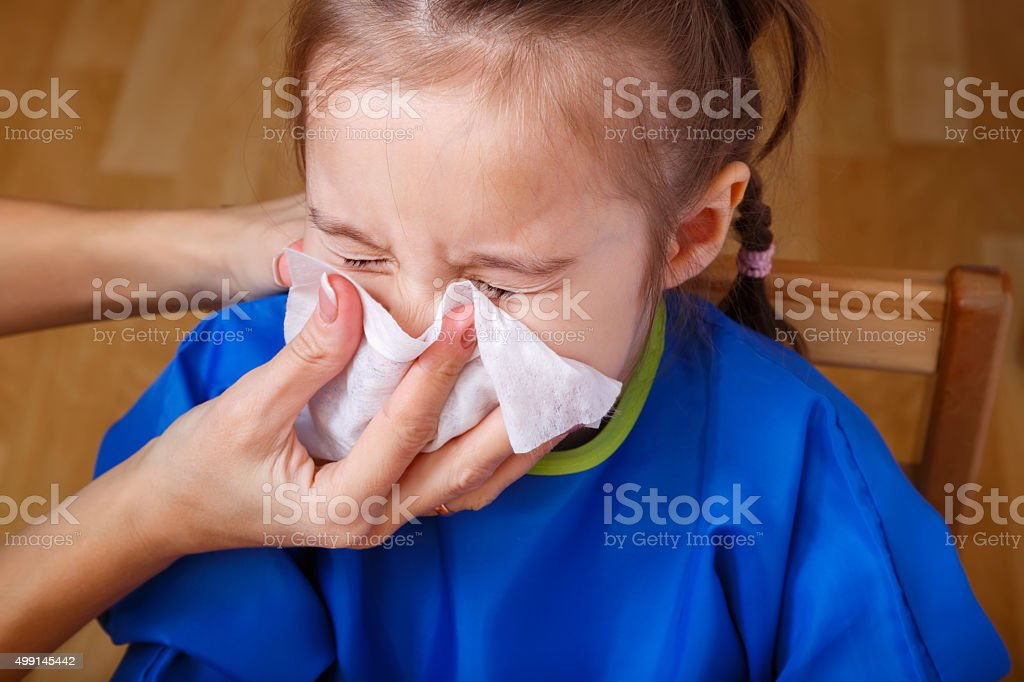 Parent hand helping little girl to blow her nose stock photo