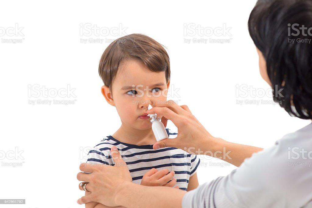 parent of a girl applies a nasal spray stock photo