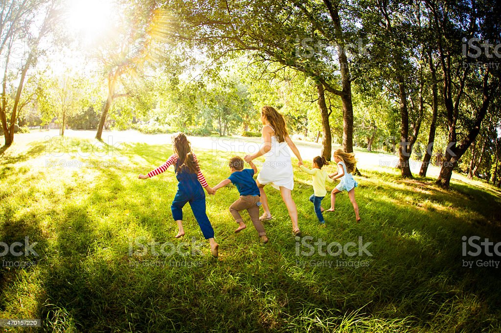 Parent running with kids through a sunlit park stock photo